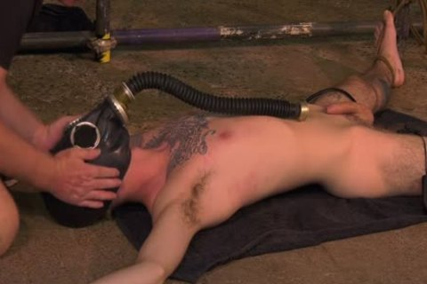 Roped Down twink acquires A Gas Mask And A coarse cook jerking